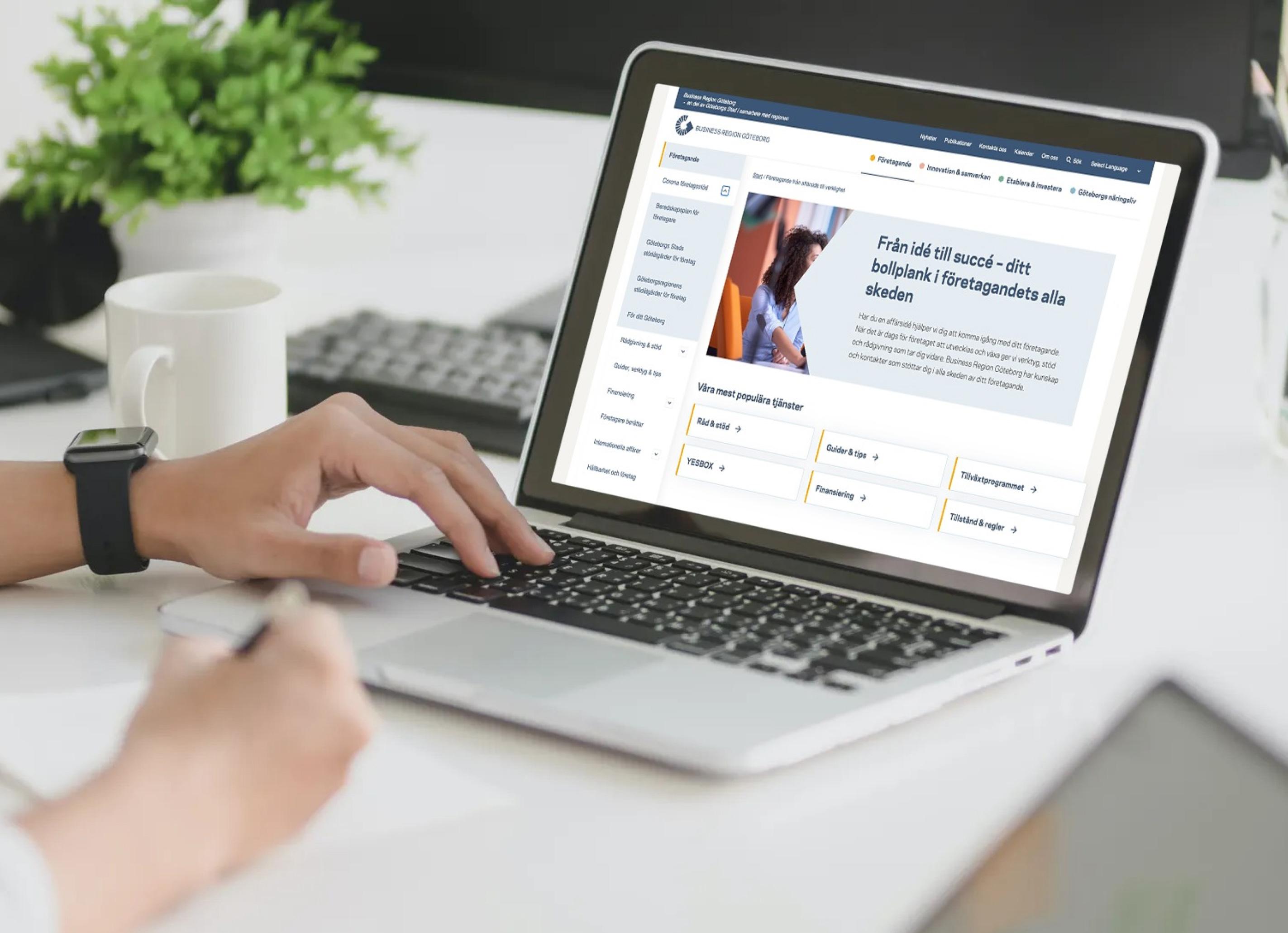 Kvinna använder sin laptop för att navigera på Business region Göteborgs nya hemsida
