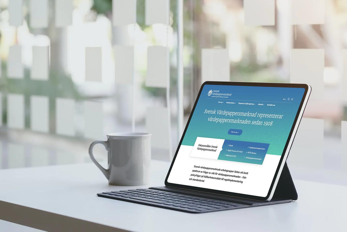 Svensk Värdepappersmarknads nya webbplats visas i en ipad som står på ett bord med en kaffemugg bredvid
