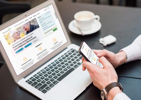 Person håller i en mobiltelefon framför en laptop. Båda enheterna visar Äldrecentrums nya hemsida