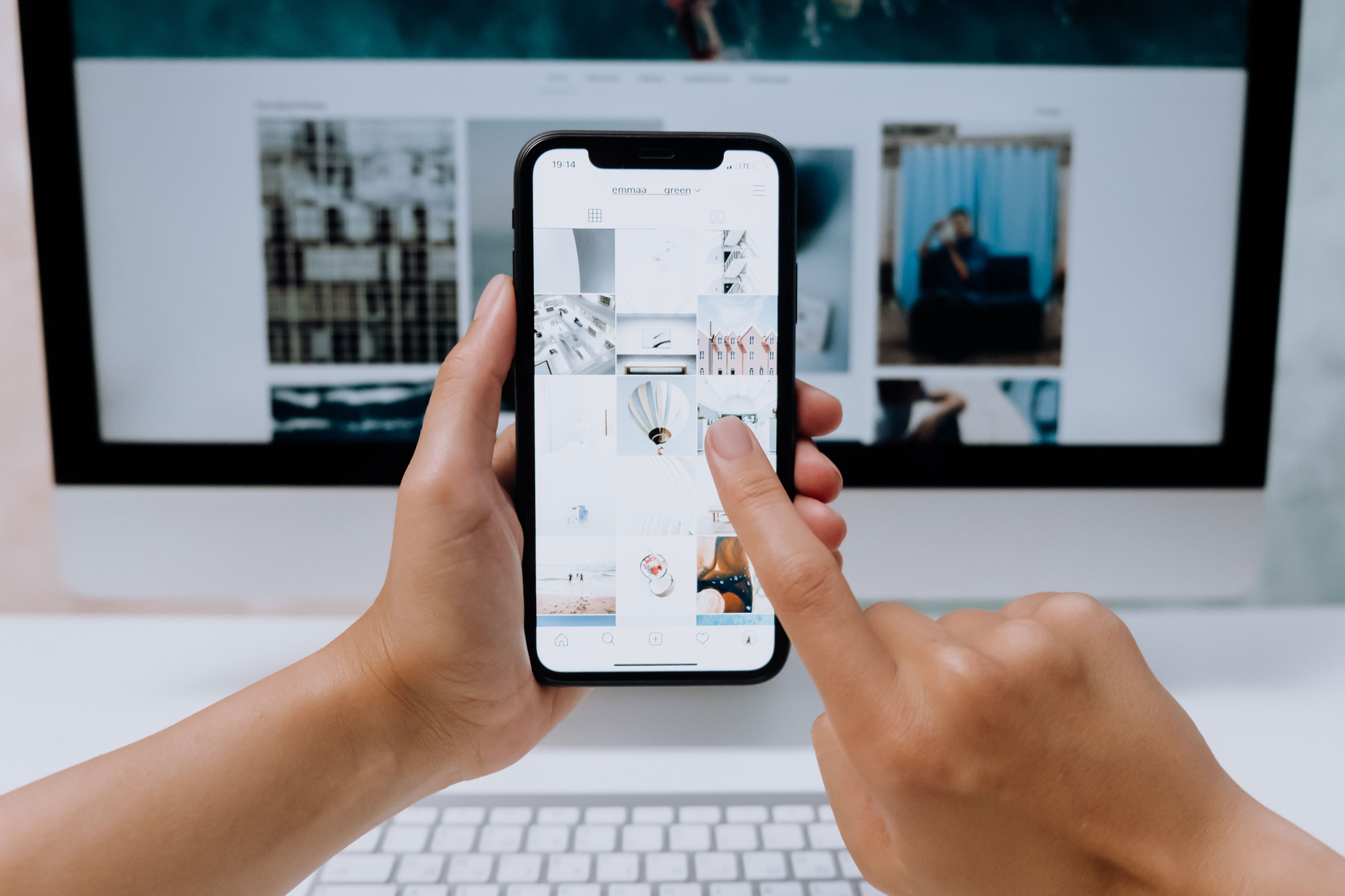 Person håller i en iphone och kollar på bilder