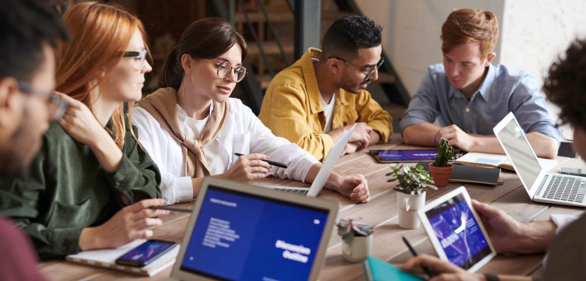 Grupp med personer sitter vid ett bord och samarbetar med sina datorer