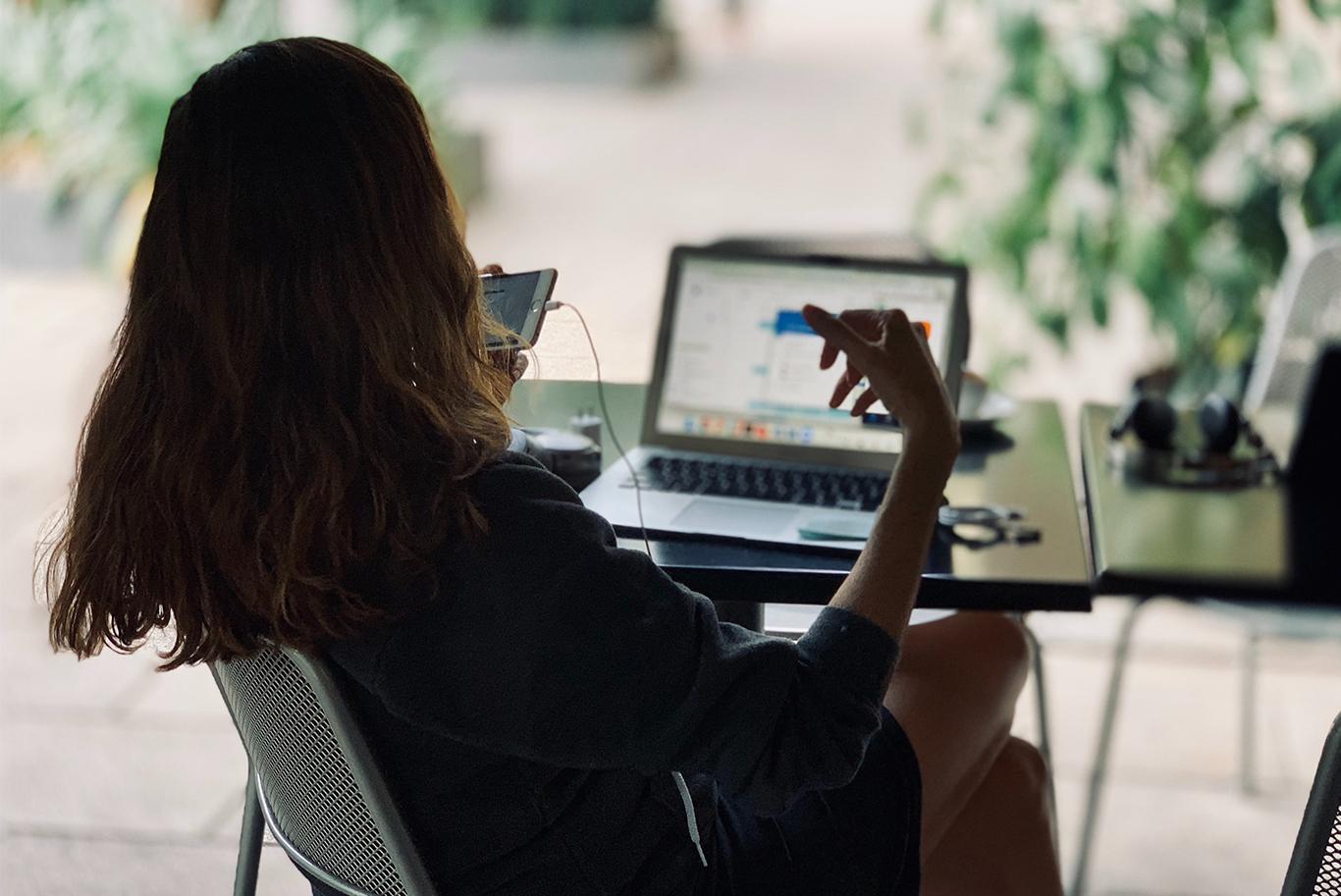 Kvinna sitter framför en laptop och pratar i sin mobiltelefon